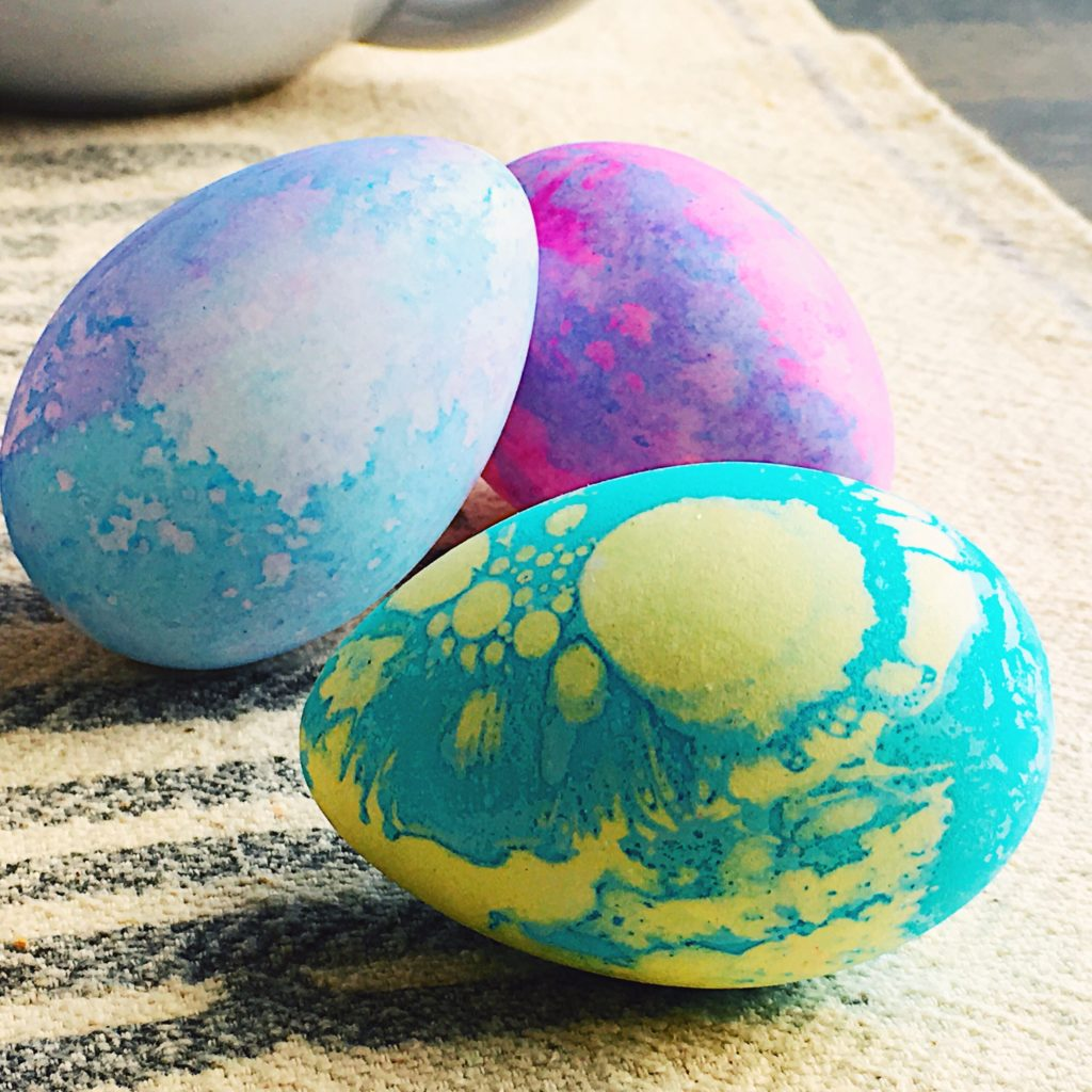 Three colored eggs on kitchen towel